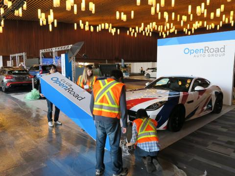 OpenRoad staff members assemble their booth for the 2016 Vancouver International Auto Show